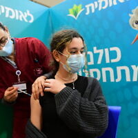 An Israeli student receives a COVID-19 vaccine injection, at a Leumit vaccination center in Tel Aviv, on January 23, 2021. (Avshalom Sassoni/Flash90)