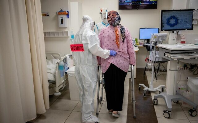 Shaare Zedek hospital team member wearing safety gear help a pregnant woman at the Coronavirus ward of Shaare Zedek hospital in Jerusalem on February 3, 2021 (Yonatan Sindel/Flash90)