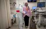 A pregnant woman gets help walking at the coronavirus ward of Shaare Zedek hospital in Jerusalem, on February 3, 2021. (Yonatan Sindel/Flash90)
