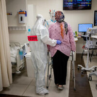 A pregnant woman gets help walking at the coronavirus ward of Shaare Zedek hospital in Jerusalem, on February 3, 2021. (Yonatan Sindel/Flash90)