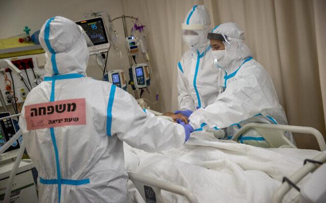 Family members wearing safety gear visit a family member at the coronavirus ward of Shaare Zedek hospital in Jerusalem on February 3, 2021. (Yonatan Sindel/Flash90)