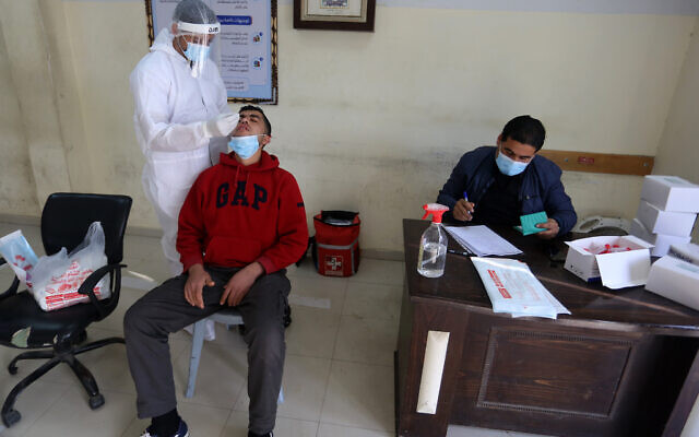 A Palestinian health worker takes samples for coronavirus at a health center in Rafah, in the southern Gaza Strip, on February 4, 2021. (Abed Rahim Khatib/Flash90)