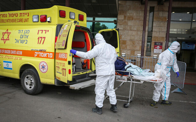 Magen David Adom workers wearing protective clothing evacuate a patient to the coronavirus unit at Ziv Medical Center in the Northern Israeli city of Safed, on February 4, 2021. (David Cohen/Flash90)