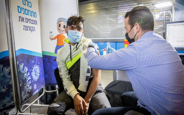 A young Israeli receives a COVID-19 vaccine shot, at Clalit vaccination center in Jerusalem, on February 4, 2021. (Yonatan Sindel/Flash90)