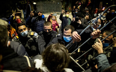 Demonstrators scuffle with police during a protest against Israeli prime minister Benjamin Netanyahu outside the PM's official residence in Jerusalem, February 6, 2021. (Yonatan Sindel/Flash90)