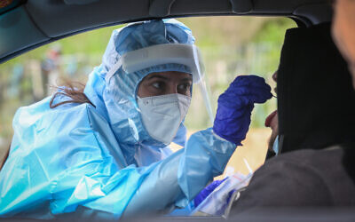 A medical worker at a drive-through site to collect samples for coronavirus testing in the northern Israeli city of Safed on February 8, 2021. (David Cohen/Flash90)