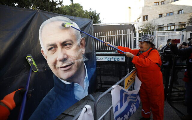 Protester dressed up as a cleaner demonstrates outside the official residence of Prime Minister Benjamin Netanyahu in Jerusalem, as Netanyahu is due at his trial at the Jerusalem District Court, February 8, 2021. (Olivier Fitoussi/Flash90)
