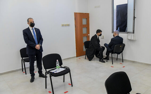 Prime Minister Benjamin Netanyahu (seated beneath a window) before a hearing at the District Court in Jerusalem on February 8, 2021. Netanyahu is charged with fraud and breach of trust in three cases and bribery in one of them. (Reuven Kastro/POOL)
