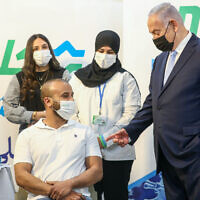 Prime Minister Benjamin Netanyahu (R) during a visit to a COVID-19 vaccination center in Zarzir, northern Israel, February 9, 2021. (David Cohen/Flash90)
