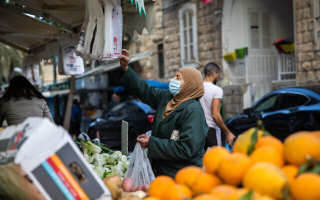 Illustrative: A woman shops in Wadi Nisnas in Haifa on February 5, 2021. (Shir Torem/Flash90)