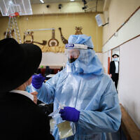 A medical worker tests an ultra-Orthodox man for coronavirus in Safed on February 10, 2021. (David Cohen/Flash90)