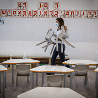 "Vered Brosh, the school principal, arranges the class for reopening at ""Israeli school Beit Hakerem"" in Jerusalem on February 10, 2021. (Yonatan Sindel/Flash90)"