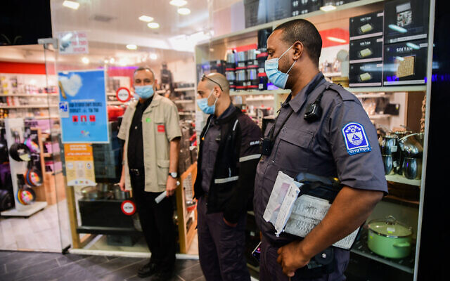 Police and inspectors of the Bat Yam municipality enforce a COVID-19 lockdown at a mall in Bat Yam that was partially opened against government regulations, on February 11, 2021. (Avshalom Sassoni/Flash90)