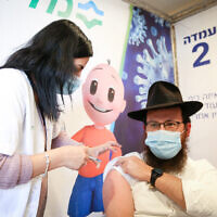 A man receives a COVID-19 vaccine at a vaccination centerl in Safed, on February 14, 2021. (David Cohen/Flash90)
