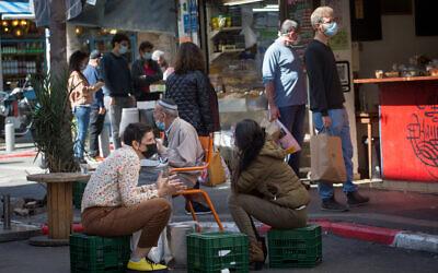 Israelis sit in the sun in Tel Aviv, on February 14, 2021. (Miriam Alster/ FLASH90)
