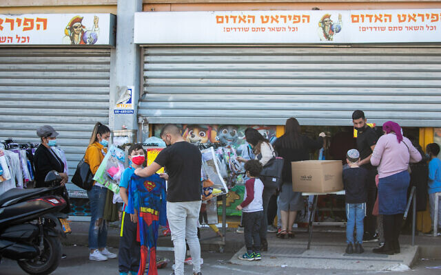 Israelis shop for costumes at a Red Pirate toy store in Kiryat Ekron, ahead of the Jewish holiday of Purim, on February 14, 2021 (Yossi Aloni/FLASH90)