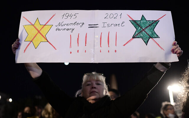 A protester apparently compares Israel's green vaccination certification to the Nazi laws forcing Jews to wear yellow stars in Tel Aviv, on February 15, 2021 (Tomer Neuberg/FLASH90)