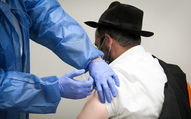 An Israeli man receives a vaccine at a Meuhedet COVID-19 vaccination center in Kfar Chabad, on February 16, 2021. (Flash90)