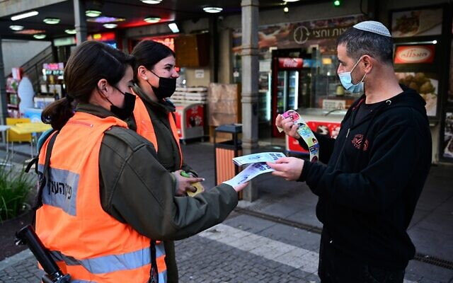 Soldiers from the Home Front command give out COVID-19 information in Katzrin, February 16, 2021 (Michael Giladi/Flash90)