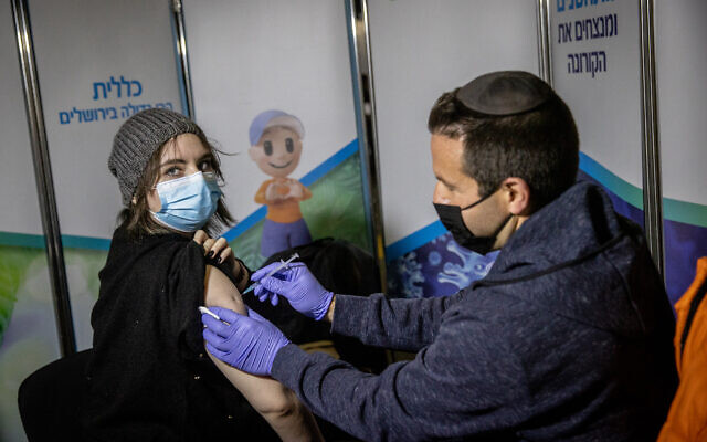 An Israeli woman receives a COVID-19 vaccine at a Clalit vaccination center in Jerusalem on February 16, 2021. (Yonatan Sindel/Flash90)