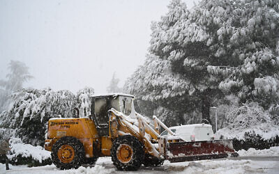 A tractor clears the snow off the ground in Kibbutz Marom Golan, in the Golan Heights February 17, 2021 (Michael Giladi/Flash90)