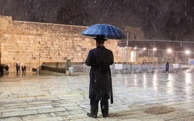 Snow falls at the Western Wall in Jerusalem's Old City, February 17, 2021. (Noam Revkin/Flash90)