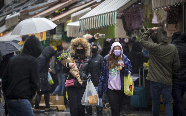People wearing face masks take cover from the rain as they shop for groceries at the Mahane Yehuda Market in Jerusalem, on February 19, 2021. (Olivier Fitoussi/Flash90)