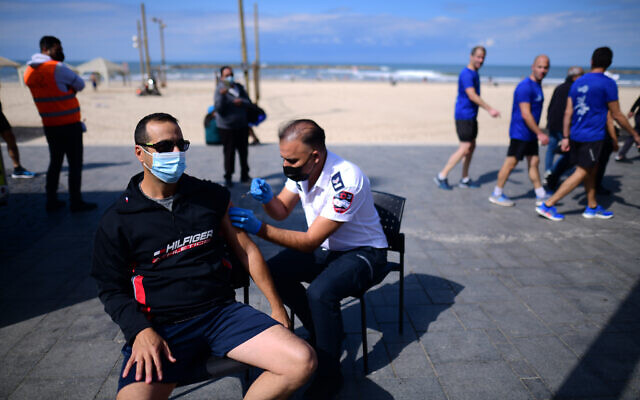 Israelis receives a Covid-19 vaccine injection at a Covid-19 mobile vaccine station on the beach in Tel Aviv, February 20, 2021 (Tomer Neuberg/Flash90)