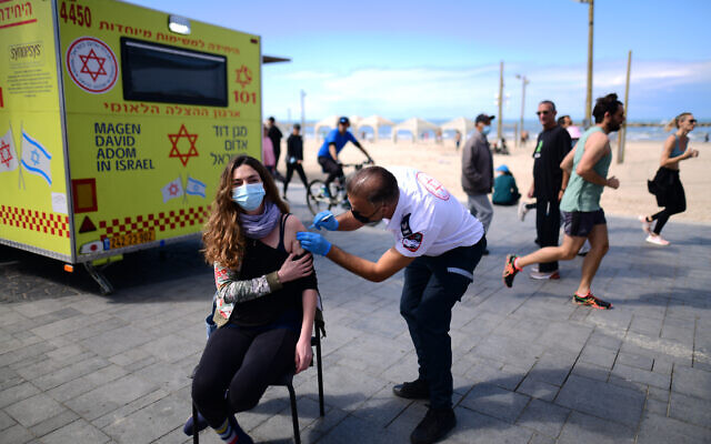 Israelis receive a COVID-19 vaccine injection at a mobile vaccine station on the beach in Tel Aviv, February 20, 2021. (Tomer Neuberg/Flash90)