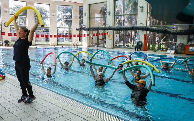 People swim at the Holmes Place health club in Modiin on February 21, 2021, after it was opened for people who have been vaccinated or have recovered from COVID-19 (Yossi Aloni/Flash90)