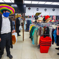 Jewish ultra-Orthodox young men search for costumes ahead the holiday of Purim in the city center of Jerusalem on February 22, 2021. (Olivier Fitoussi/Flash90)