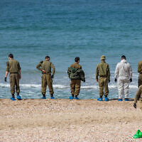 Israeli soldiers clean tar off the Palmachim beach following an offshore oil spill which hit most of the Israeli coastline. February 22, 2021. (Yonatan Sindel/Flash90)
