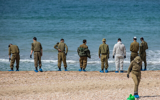 Israeli soldiers clean tar off the Palmachim beach following an offshore oil spill which drenched most of the Israeli coastline. February 22, 2021. (Yonatan Sindel/Flash90 *** Local Caption)