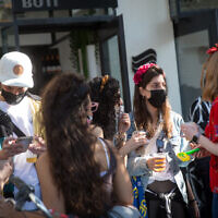Israelis dressed up in Purim costumes at Dizengoff Square in Tel Aviv on February 25, 2021. (Miriam Alster/Flash90)