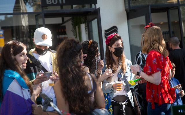 Israelis dressed up in Purim costumes at Dizengoff Square in Tel Aviv on February 25, 2021. (Miriam Alster/Flash90)