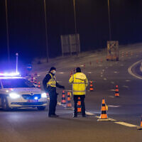 Police put up a temporary roadblock on Route 1 near Jerusalem during a nighttime curfew for the Jewish holiday of Purim, February 25, 2021 (Yonatan Sindel/Flash90)