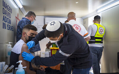 East Jerusalem residents receive COVID-19 vaccine injections in a mobile Magen David Station at the Damascus Gate in the Old City of Jerusalem on February 26, 2021. (Olivier Fitoussi/Flash90)