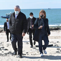 Prime Minister Benjamin Netanyahu, left, and Environmental Protection Minister Gila Gamliel walk on Ashdod beach on February 21, 2021, after an offshore oil spill caused damage along Israel's Mediterranean coast (Kobi Gideon / GPO)