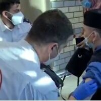 A MDA medic vaccinates a Palestinian worker in East Jerusalem on February 10, 2021 (Screencapture/Twitter)