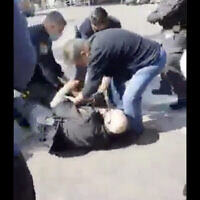 Police officers wrestle a shop owner in Holon to the ground to prevent him from stabbing himself, after he was fined for putting his merchandise on the sidewalk, February 24, 2021. (Screen capture: Twitter)