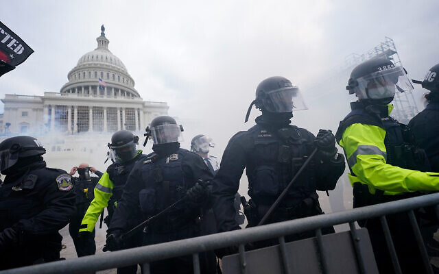 Police stand guard against Trump supporters at the US Capitol, Washington, January 6, 2021. (AP Photo/Julio Cortez, File)