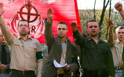 Tomasz Greniuch, in the center holding papers, makes a gesture that appears to be a Nazi salute at a far-right event in Poland in 2007. (Bartosz Siedlik, courtesy of Gazeta Wyborcza via JTA)