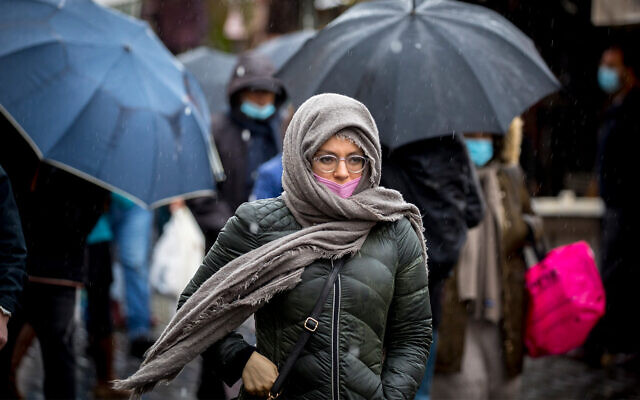 People wearing face masks take cover from rain at the Mahane Yehuda market in Jerusalem, on February 19, 2021. (Olivier Fitoussi/Flash90)