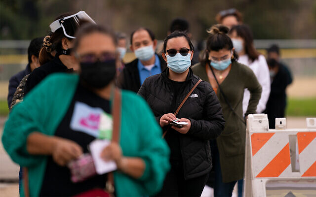 People wait in line to get COVID-19 vaccine shots at a vaccination site in Los Angeles, California, Feb. 9, 2021. (AP Photo/Jae C. Hong)
