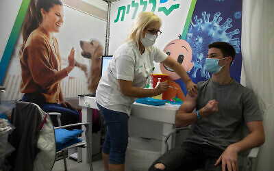 An Israeli youth receives a Pfizer-BioNTech COVID-19 vaccine during an event to encourage the vaccination of young Israelis at a vaccination center in Holon, near Tel Aviv, Feb. 15, 2021. (AP Photo/Sebastian Scheiner)