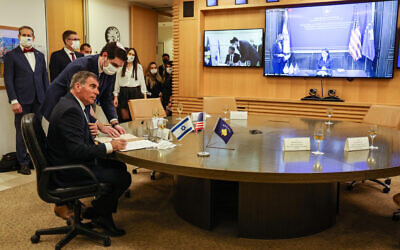 Foreign Minister Gabi Ashkenazi signs a joint declaration establishing ties with Kosovo during an official ceremony held over Zoom with his counterpart from Kosovo, Meliza Haradinaj Stublla, onscreen, at the Israeli Foreign Ministry headquarters in Jerusalem on February 1, 2021. (Menahem Kahana/AFP)