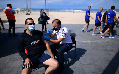 A man receives a COVID-19 vaccine injection at a mobile vaccine station on the beach in Tel Aviv, February 20, 2021. (Tomer Neuberg/Flash90)