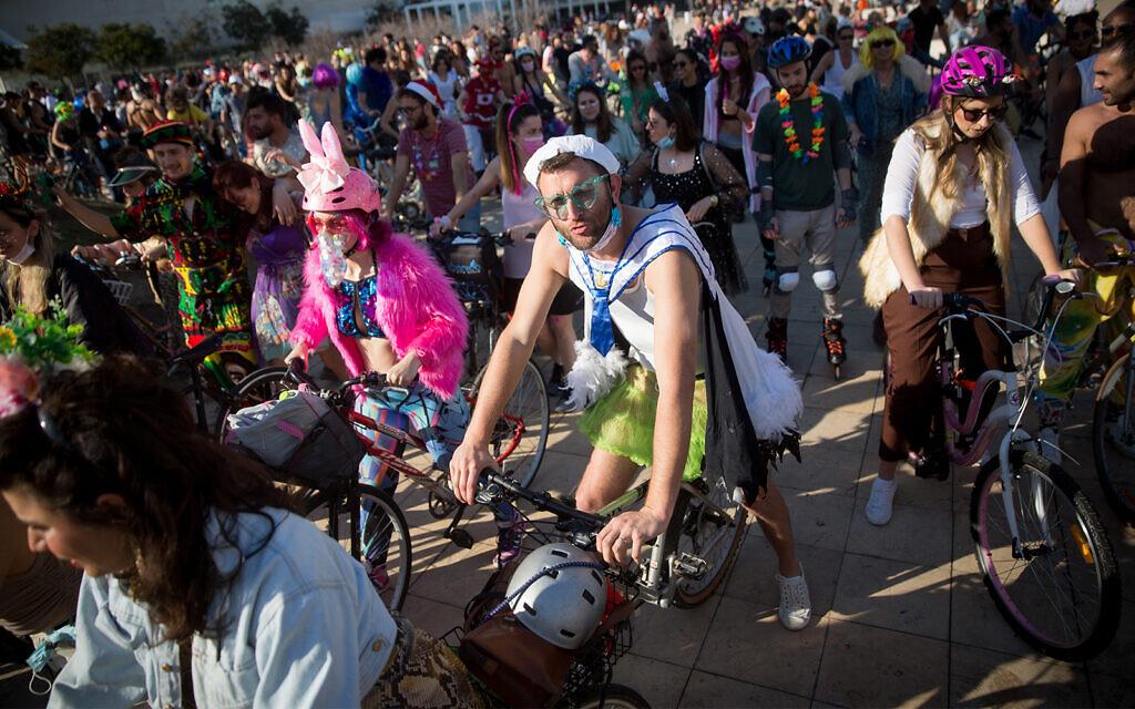 People wearing costumes celebrate  Purim at Habima Square in Tel Aviv, February 26, 2021. (Miriam Alster/Flash90)