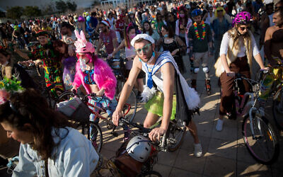 People wearing costumes celebrate  Purim at Habima Square in Tel Aviv, February 26, 2021. (Miriam Alster/Flash90)