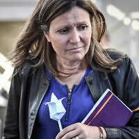 President of the Laws Commision at the French National Assembly Yael Braun-Pivet holds a paper flower offered by a man at the 'Centre de Retention Administrative' (CRA), a migrant detention centre in Vincennes, eastern Paris, on September 18, 2019. (STEPHANE DE SAKUTIN/AFP via Getty Images)